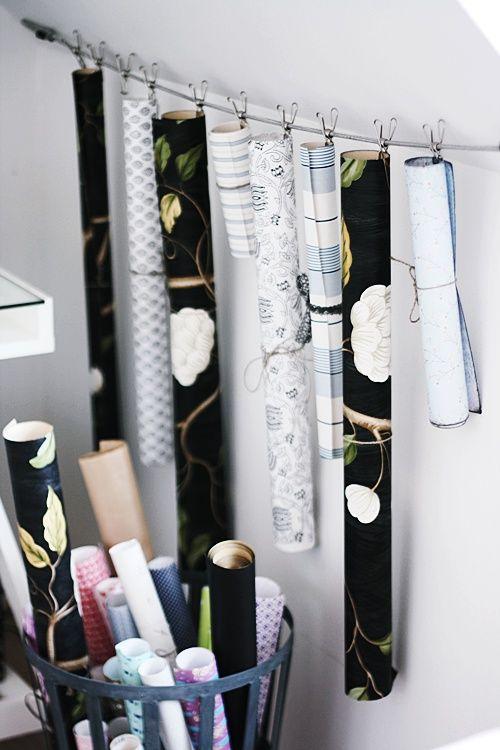 Úložné prostory můžeme řešit i netradičně - třeba vzorky tapet navěsit s pomocí kolíčků na lanko nebo dát do košíku. Zdroj foto.